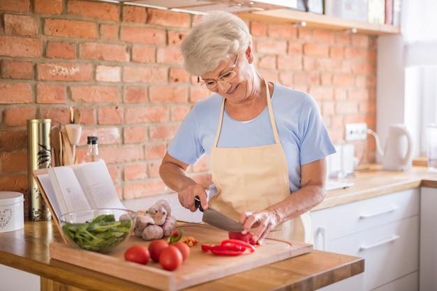 Ältere frau, die gemüse schneidet
