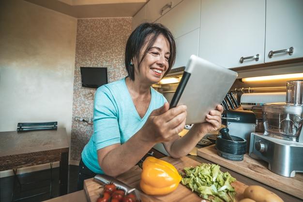 Ältere frau, die gemüse zu hause beim lesen eines rezepts auf der tablette kocht.