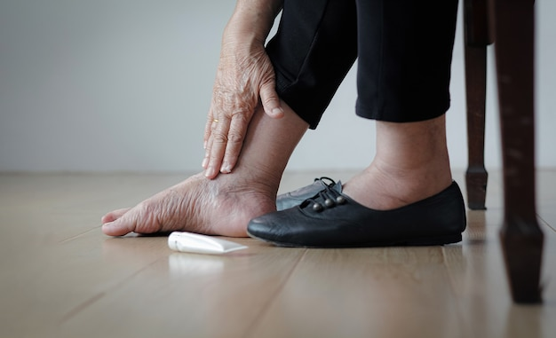 Ältere frau, die geschwollene füße eincremet, bevor sie schuhe anzieht