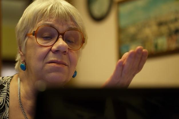 Ältere frau, die gestikuliert, wie sie auf laptop liest