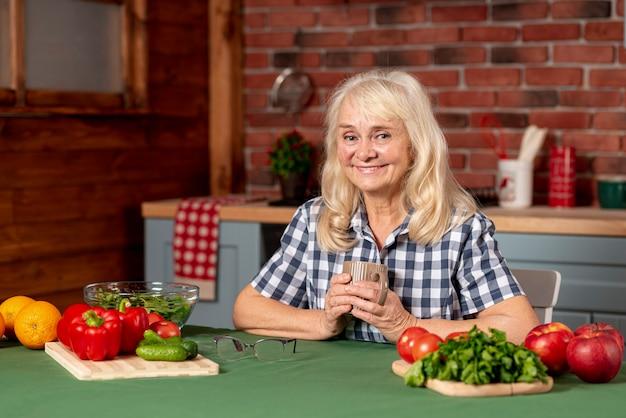 Ältere frau, die gesundes lebensmittel kocht