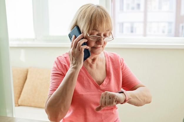 Ältere frau, die gesundheit mit smartwatch prüft und mit familie auf smartphone spricht