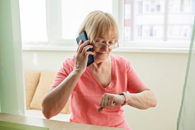 Ältere frau, die gesundheit mit smartwatch prüft und mit familie auf smartphone spricht Premium Fotos