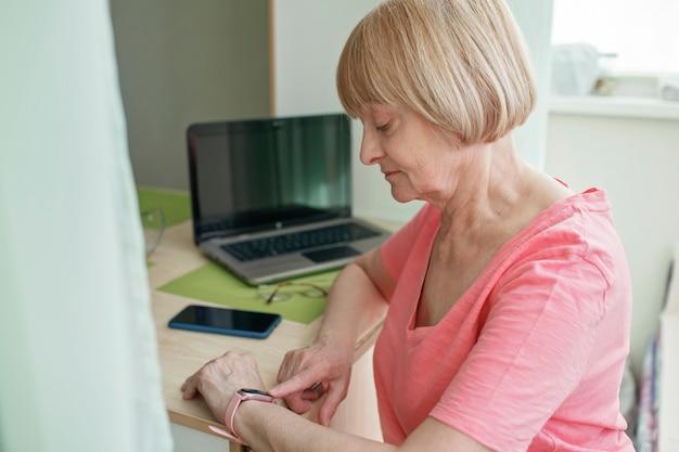 Ältere frau, die gesundheitsinformationen unter verwendung der intelligenten uhr prüft