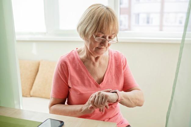 Ältere frau, die gesundheitsinformationen unter verwendung der modernen gesundheitsversorgung und der unterstützung der intelligenten uhr prüft
