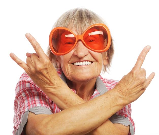 Ältere frau, die große sonnenbrille trägt, die funky aktion lokalisiert auf weiß tut