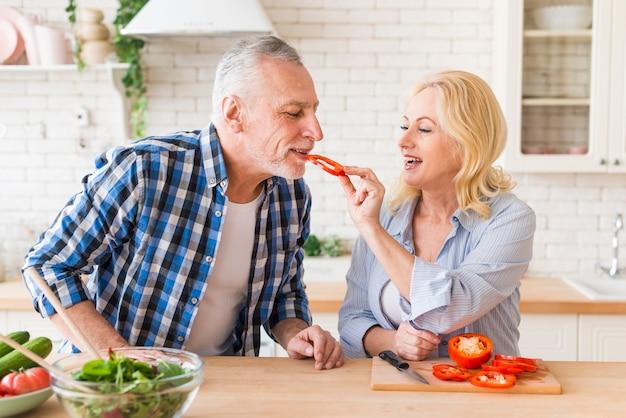 Ältere frau, die grünen paprika zu ihrem ehemann in der küche einzieht