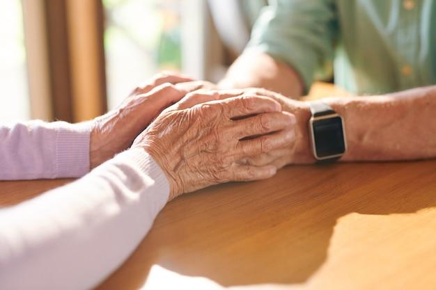 Ältere frau, die hände ihres mannes in not hält, während beide am holztisch voreinander sitzen