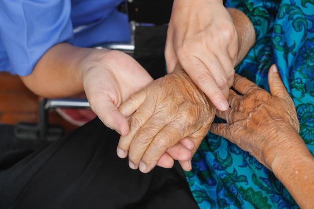 Ältere frau, die hand mit pfleger hält