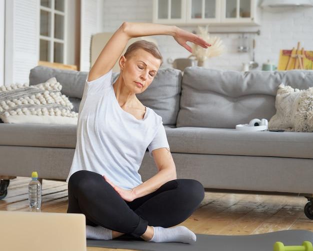Ältere frau, die hand-online-training mit laptop im wohnzimmer ausdehnt, trainieren für das wohlbefinden