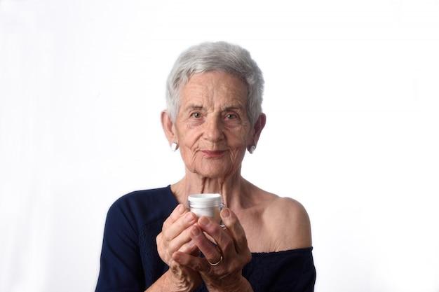 Ältere frau, die hautcreme oder feuchtigkeitscreme an ihrem gesicht aufträgt