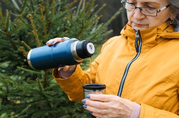 Ältere frau, die heißen tee im wald draußen gießt. porträt einer älteren frau, die in kaltem wetter geht.