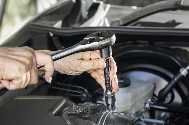 Ältere frau, die ihr auto repariert