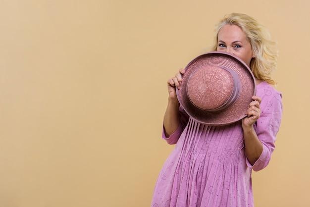 Ältere frau, die ihr gesicht mit einem rosa hut bedeckt
