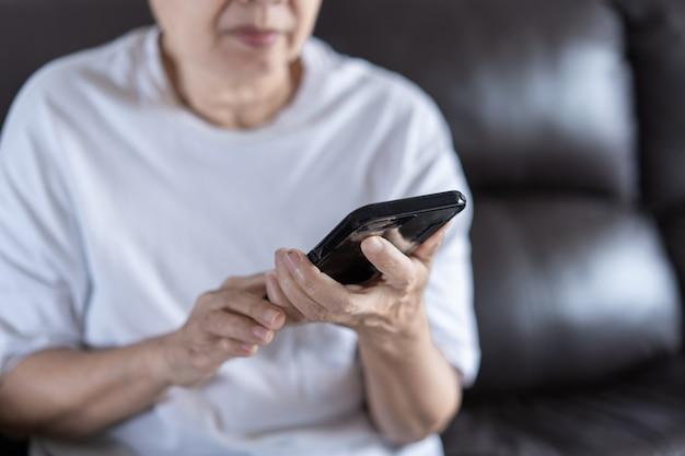 Ältere frau, die ihr telefon im haus verwendet