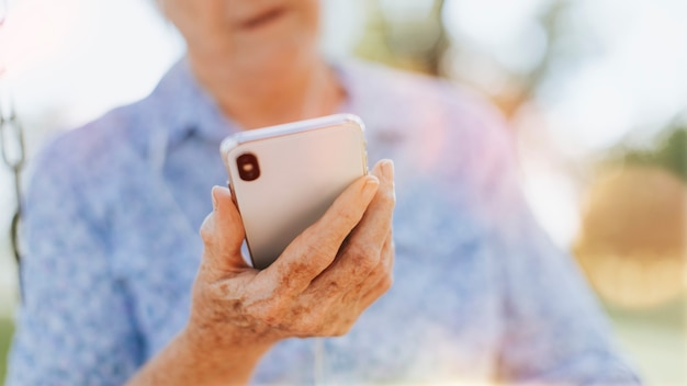 Ältere frau, die ihr telefon in einem park benutzt
