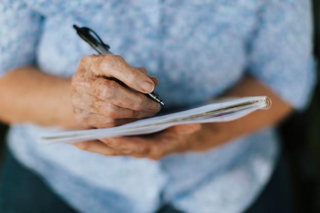 Ältere frau, die ihre erinnerungen in ein notizbuch notiert