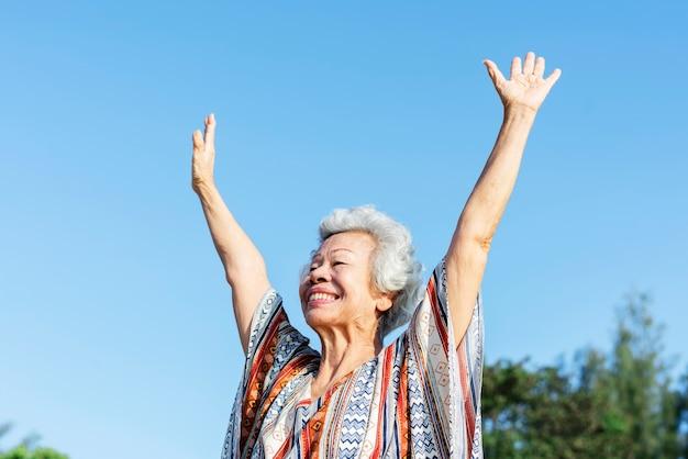 Ältere frau, die ihre hände anhebt