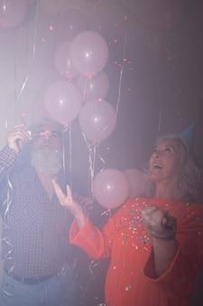 Ältere frau, die ihre schlagseifenblasen des ehemanns in der geburtstagsfeier betrachtet