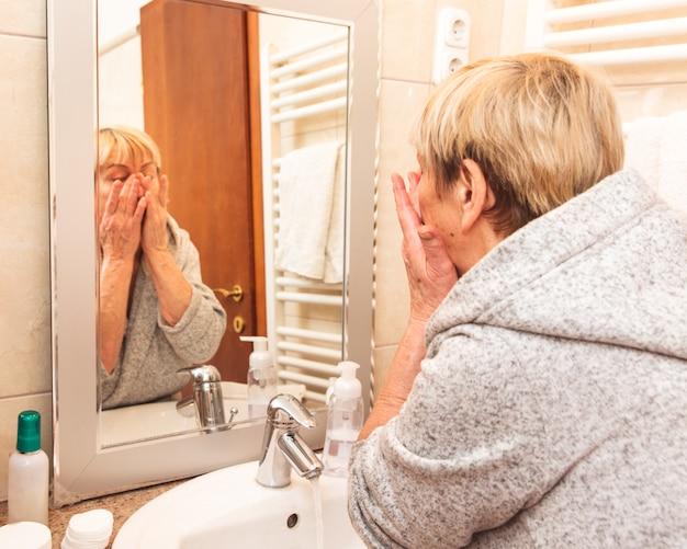 Ältere frau, die ihre weiche gesichtshaut berührt