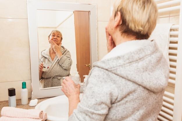 Ältere frau, die ihre weiche gesichtshaut, zu hause schauend im spiegel berührt