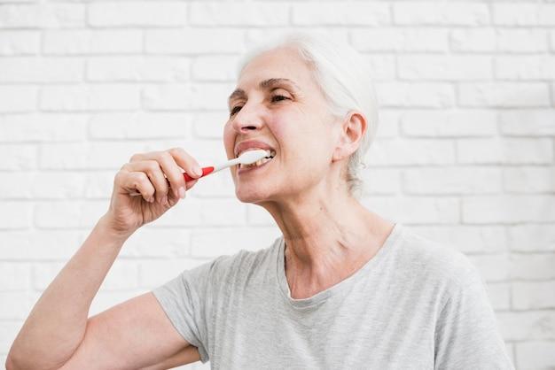 Ältere frau, die ihre zähne wäscht