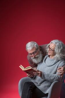 Ältere frau, die ihren ehemann betrachtet im buch gegen roten hintergrund betrachtet