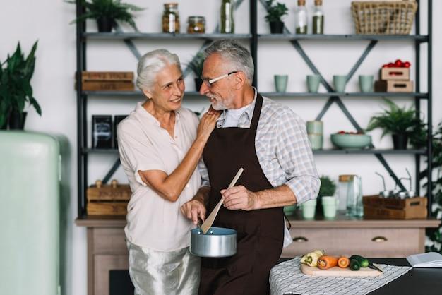 Ältere frau, die ihren ehemann zubereitet lebensmittel in der küche betrachtet
