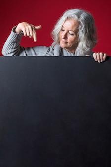 Ältere frau, die ihren finger abwärts auf leeres schwarzes plakat gegen roten hintergrund zeigt