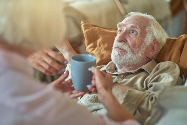 Ältere frau, die ihren kranken ehepartner anschaut und tee anbietet