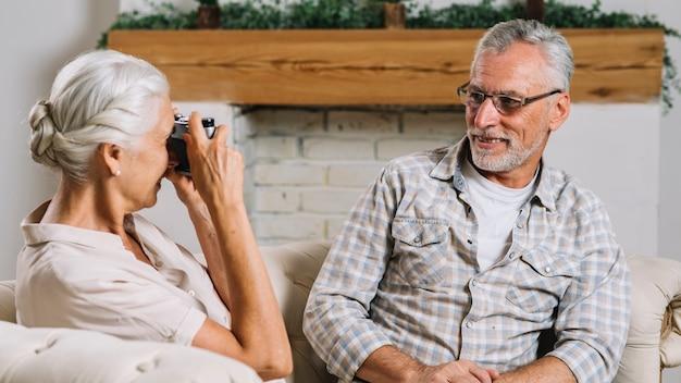 Ältere frau, die ihren lächelnden ehemann mit kamera fotografiert