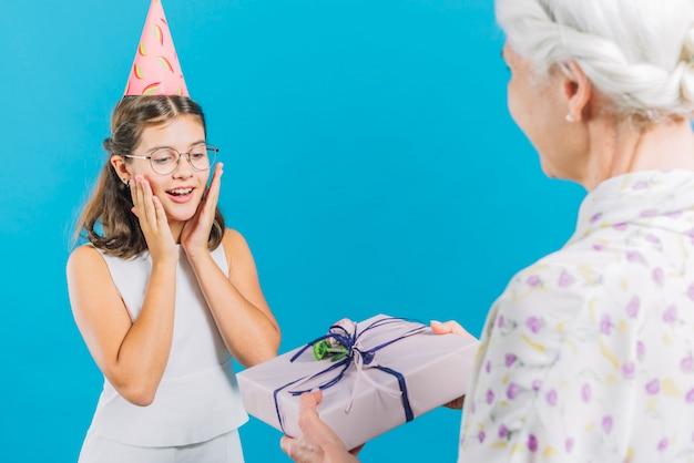 Ältere frau, die ihrer enkelin auf blauem hintergrund geburtstagsgeschenk gibt