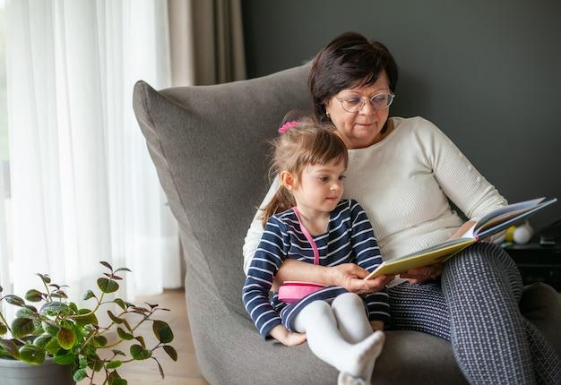 Ältere frau, die ihrer enkelin ein buch vorliest und auf einem sitzsack sitzt. oma erzählt dem kleinen mädchen geschichten.
