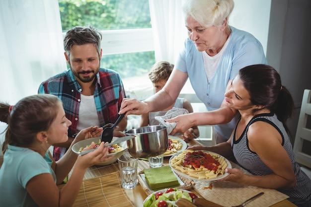 Ältere frau, die ihrer familie mahlzeit serviert