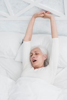 Ältere frau, die im bett aufwacht