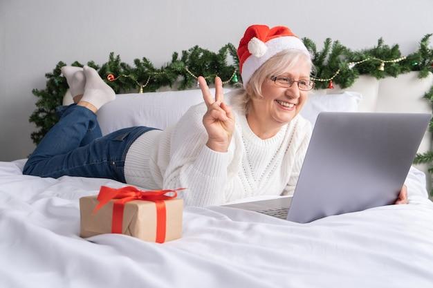 Ältere frau, die im bett liegt und videoanruf mit familie