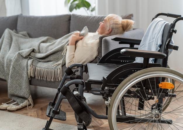 Ältere frau, die im bett neben einem rollstuhl liegt