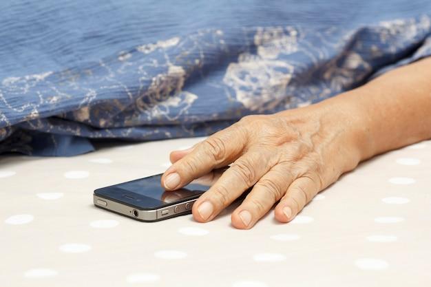 Ältere frau, die im bett schläft und ein handy hält.