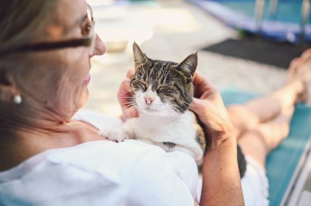 Ältere frau, die im garten mit einer katze entspannt
