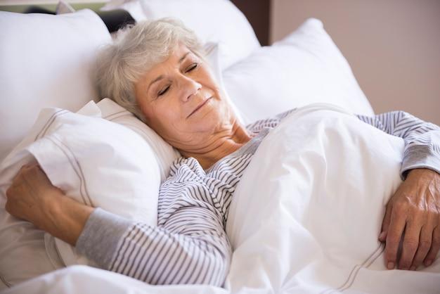 Ältere frau, die im großen bett schläft