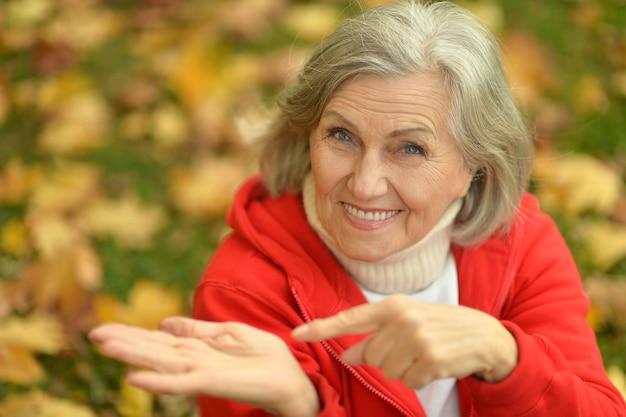 Ältere frau, die im herbst im park daumen zeigt