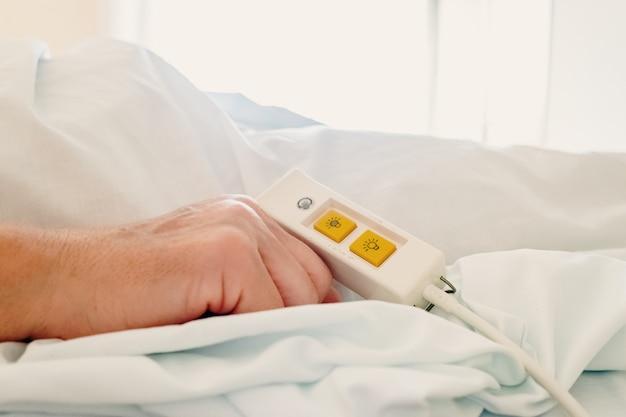 Ältere frau, die im krankenhausbett unter verwendung des unterstützungsbefehls für hilfe liegt.