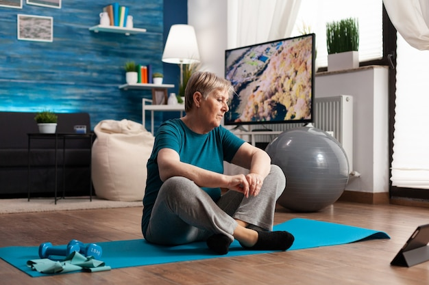 Ältere frau, die im lotussitz auf yogamatte sitzt und körpermuskeln trainiert, die gewicht abnehmen