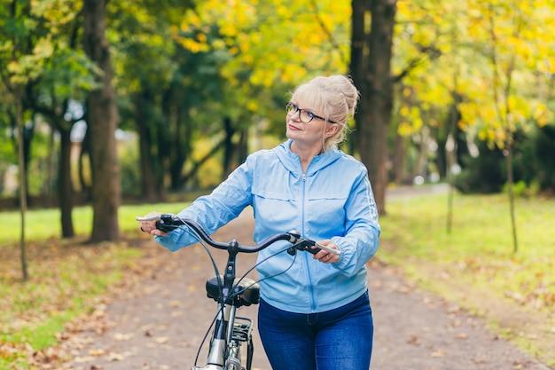 Ältere frau, die im park mit einem fahrrad geht