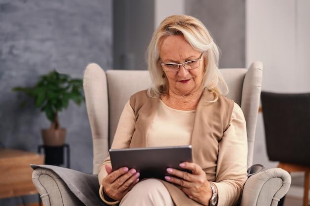 Ältere frau, die im stuhl zu hause sitzt und tablette verwendet, um an den sozialen medien zu hängen.