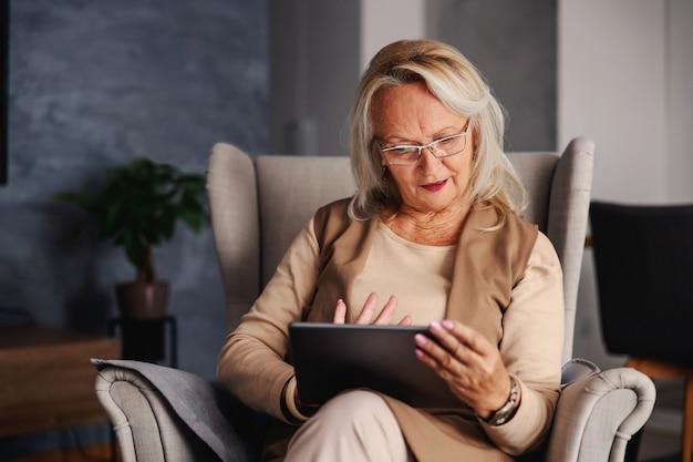 Ältere frau, die im stuhl zu hause sitzt und tablette verwendet, um an sozialen medien zu hängen.