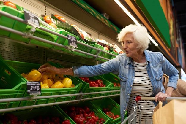 Ältere frau, die im supermarkt einkauft