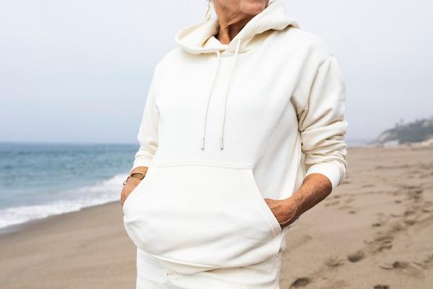 Ältere frau, die im winter am strand sich entspannt