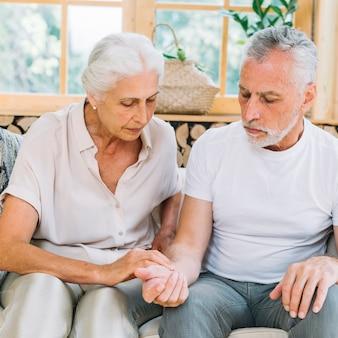 Ältere frau, die impuls ihres ehemanns überprüft