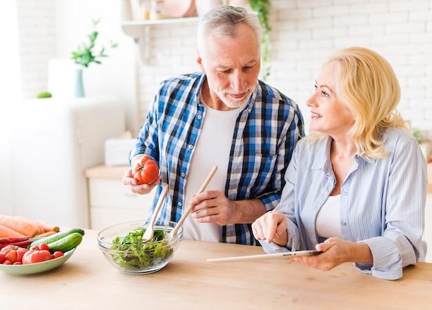 Ältere frau, die in der hand digitale tablette zeigt ihrem ehemann rezept bereitend hält den salat in der küche hält